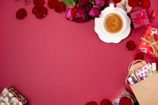 Una tazza di caffè profumato e decorazioni natalizie su sfondo rosso. rose, regali e sorprese natalizie. vista dall'alto. telaio. copia spase