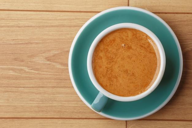 Una tazza di caffè profumato in schiuma su un tavolo di legno.