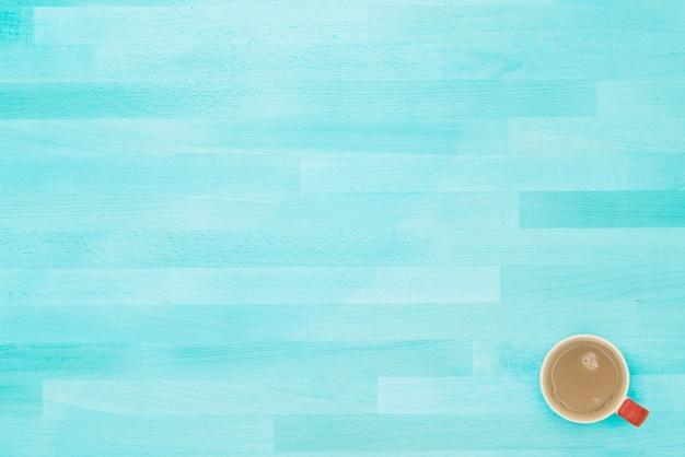 Una tazza di caffè rossa sul tavolo o sullo scrittorio di legno blu chiaro d'annata dell'ufficio di struttura dalla vista superiore.