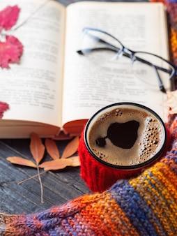 Una tazza di caffè su un tavolo di legno con un vecchio libro di foglie secche e una sciarpa colorata a maglia calda