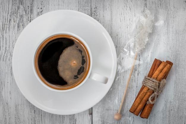 Una tazza di caffè, zucchero e bastoncini di cannella