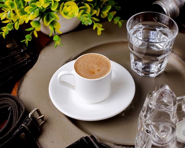 Una tazza di caldo americano e un bicchiere d'acqua