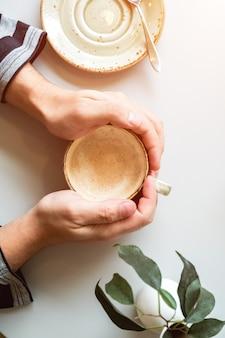 Una tazza di cappuccino su un tavolo luminoso in una caffetteria nelle mani degli uomini