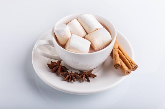 Una tazza di cioccolata calda con marshmallow e cannella isolato su bianco.