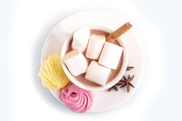 Una tazza di cioccolata calda con marshmallow, meringa e spezie isolate su bianco.