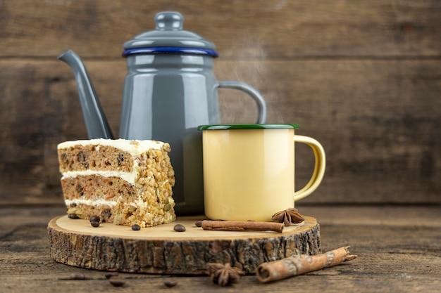 Una tazza di latta gialla di tè caldo con teiera e torta sul tavolo di legno.