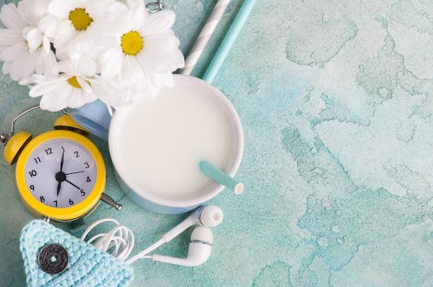 Una tazza di latte con paglia, cuffie e orologio