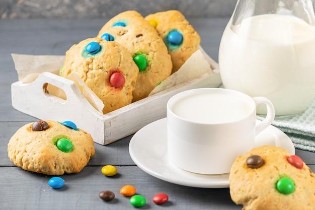 Una tazza di latte e biscotti decorati con caramelle colorate jelly bean su uno sfondo grigio. merenda per la colazione dei bambini.