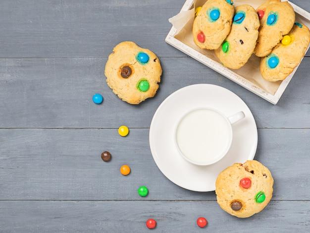 Una tazza di latte e biscotti fatti in casa decorati con caramelle colorate jelly bean su sfondo grigio. layout piatto vista dall'alto