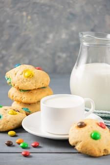 Una tazza di latte e biscotti fatti in casa decorati con caramelle colorate jelly bean