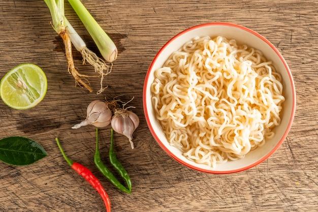 Una tazza di noodles istantanei posizionati su un tavolo di legno con lime, peperoncino, citronella e aglio come ingredienti, noodle vista dall'alto