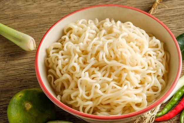 Una tazza di noodles istantanei posizionati su un tavolo di legno con lime, peperoncino e aglio come ingredienti