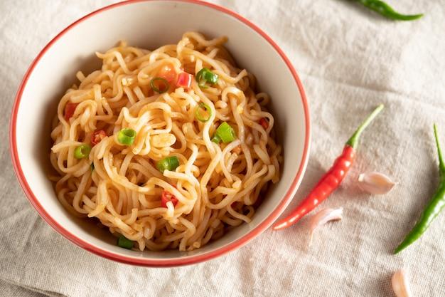 Una tazza di noodles istantanei posizionati su un tavolo di legno con peperoncino come ingredienti, vista dall'alto