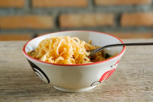 Una tazza di noodles istantanei posizionati su un tavolo di legno con peperoncino come ingredienti