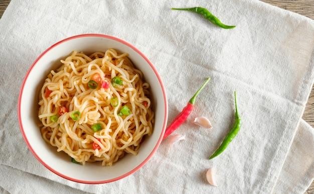 Una tazza di noodles istantanei posizionati su un tavolo di legno con peperoncino come tagliatelle e copia spazio