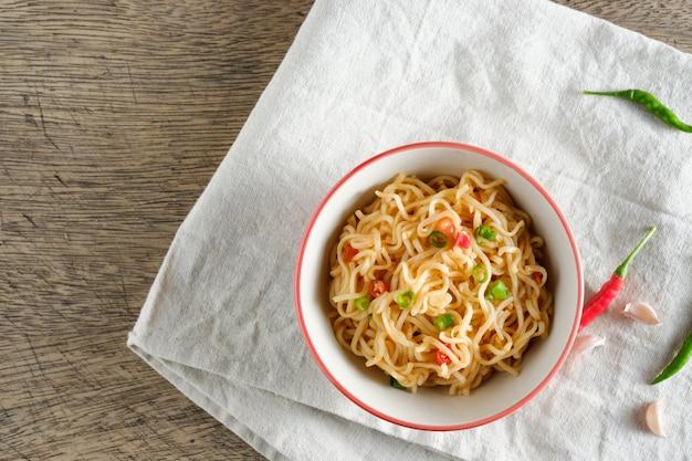 Una tazza di noodles istantanei posizionati su una napery con peperoncino come ingredienti, noodle vista dall'alto e copysapce