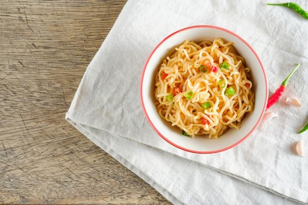 Una tazza di noodles istantanei posizionati su una napery con peperoncino come ingredienti, noodle vista dall'alto e copyspace