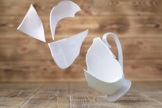 Una tazza di porcellana vintage breakout su un tavolo di legno