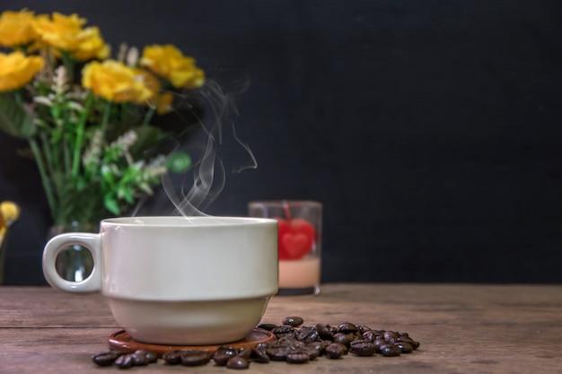 Una tazza di tazze di caffè espresso caldo e chicchi di caffè tostati disposti su fondo di pavimento in legno