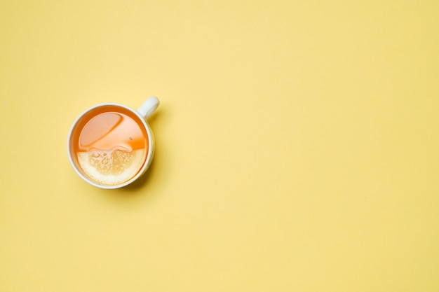 Una tazza di tè al limone su uno sfondo di carta gialla. vista dall'alto.