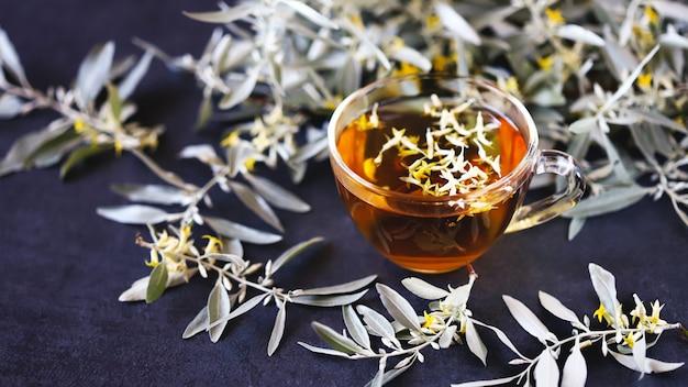 Una tazza di tè all'olivello spinoso. fiori dell'olivello spinoso in tè. tè con foglie di olivello spinoso. giovani rami e fiori dell'olivello spinoso. bevanda curativa.