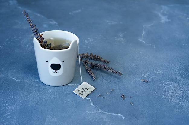 Una tazza di tè alla lavanda per sogni d'oro. fiori di lavanda su sfondo blu pietra