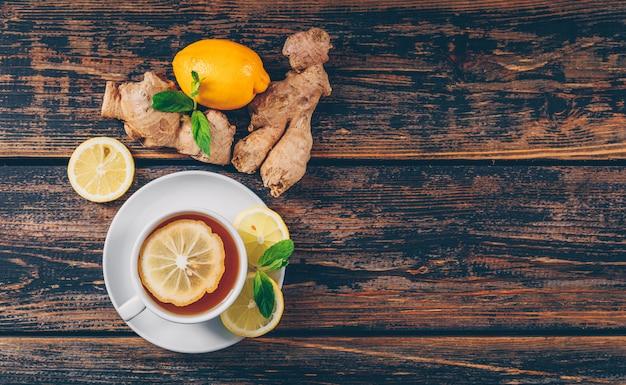 Una tazza di tè allo zenzero, piatto di limone giaceva su uno spazio di sfondo in legno scuro per il testo