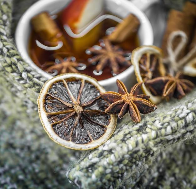 Una tazza di tè caldo con bastoncini di cannella, spezie e delizioso limone essiccato su legno con un maglione caldo