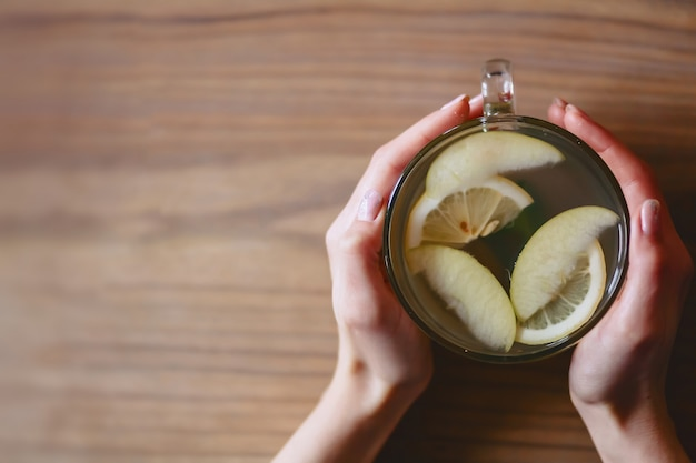 Una tazza di tè caldo con menta e limone nelle mani delle donne