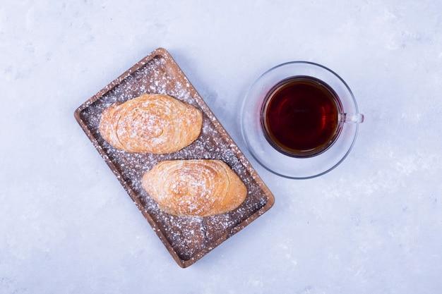 Una tazza di tè con badamburas nel piatto su fondo di legno bianco