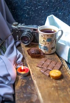 Una tazza di tè con barretta di cioccolato e muffin su un pezzo di legno.