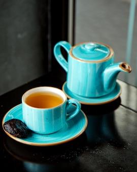 Una tazza di tè con biscotto nero