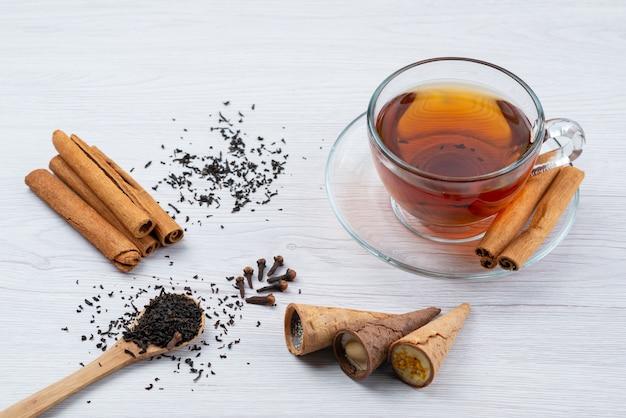Una tazza di tè con cannella e corna su bianco, dessert della colazione del tè con vista dall'alto