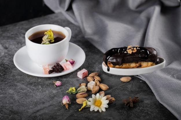 Una tazza di tè con eclair al cioccolato decorato con fiori e noci