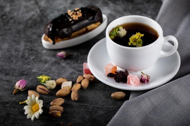Una tazza di tè con eclair al cioccolato e pistacchi su un tavolo scuro