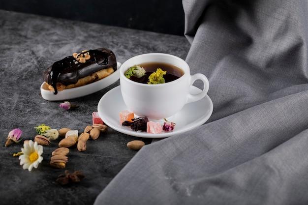 Una tazza di tè con eclair al cioccolato e pistacchi