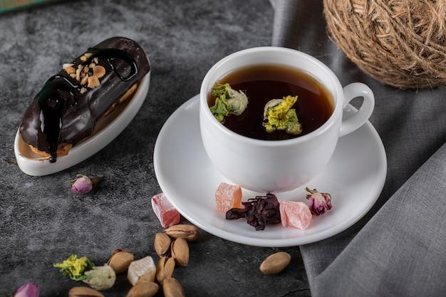Una tazza di tè con eclair al cioccolato. vista dall'alto