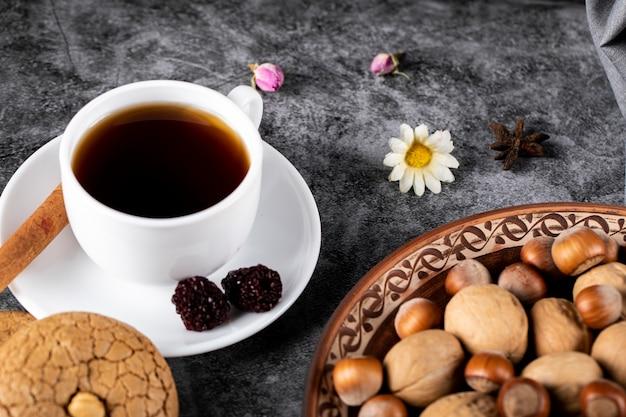 Una tazza di tè con frutti di bosco e noci