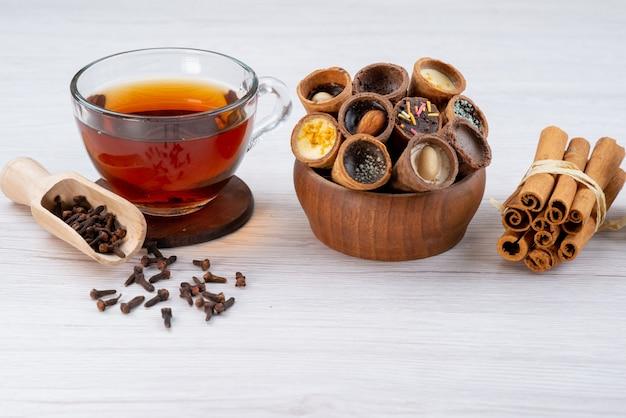 Una tazza di tè con le corna e la cannella di vista frontale su bianco, dessert della colazione del tè