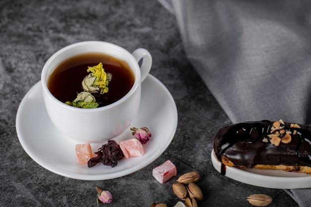 Una tazza di tè con lokum turco e eclair di cioccolato.