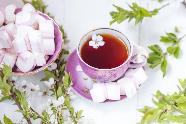 Una tazza di tè con marshmallow rosa e bianco con fiore di mela ramoscello