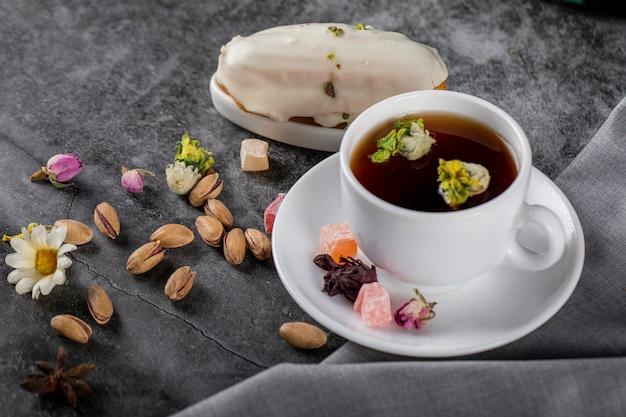 Una tazza di tè con noci e fiori in fiore