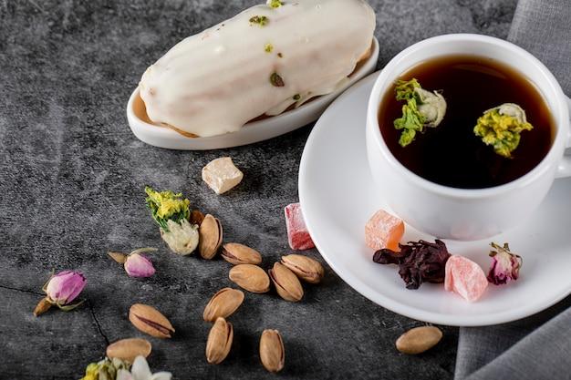 Una tazza di tè con noci e torta cremosa lattea
