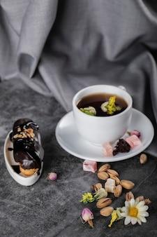 Una tazza di tè con pistacchi ed eclair di cioccolato decorato con fiori