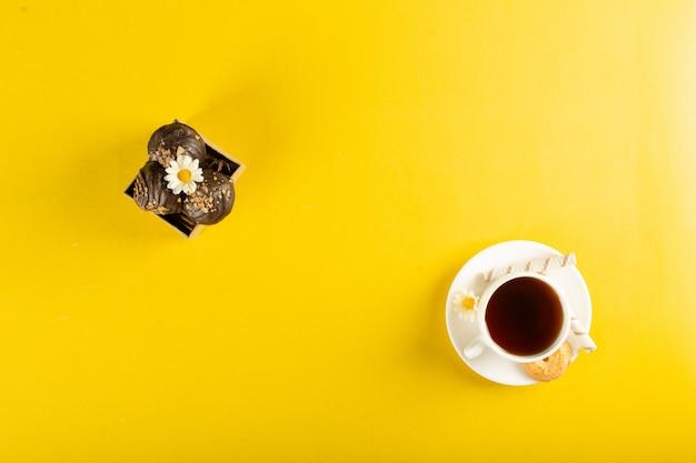 Una tazza di tè con praline al cioccolato su giallo. vista dall'alto