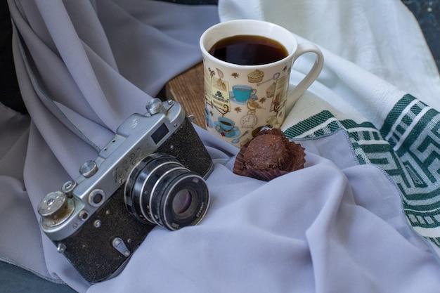 Una tazza di tè con una pralina al cioccolato sul tavolo.