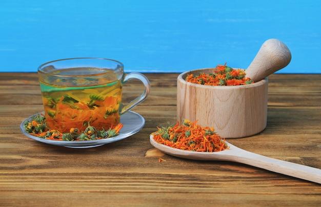 Una tazza di tè di calendula su un tavolo di legno, un mortaio con fiori di calendula su blu