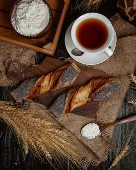 Una tazza di tè è pane su uno sfondo scuro retrò