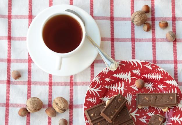 Una tazza di tè e pezzi di cioccolato nel piatto rosso.