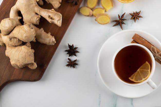 Una tazza di tè e piante di zenzero su una tavola di legno